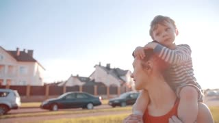 Mom and son spend time together. Cute little boy sits on his moms shoulders. Sun shines on a summer day. Slow mo