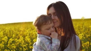 mother holding her son at field at sunset. Slow mo