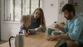 Mother is smiling at her daughter while having conversation with husband at the kitchen table. Slow mo, Steadicam shot