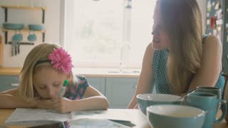 Mother is smiling while talking to her little daughter who is colouring a picture on the kitchen table. Slow mo