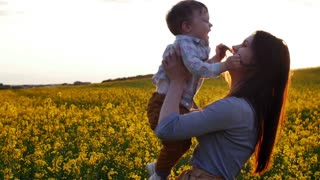 mother plays with son at field at sunset. Slow mo