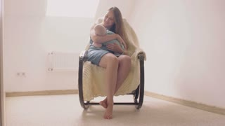 mother smiling at newborn son lulling him in a rocking chair. 4k