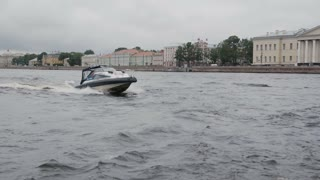 Motor boat passing by the camera. Speed boat in St Petersburg. City architecture on the quay. Slow mo,