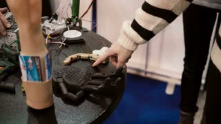 NOVEMBER 5, 2016 RUSSIA, MOSCOW Robotics Expo. Close-up of girl hand playing with mechanical finger, touch the robot. 4K