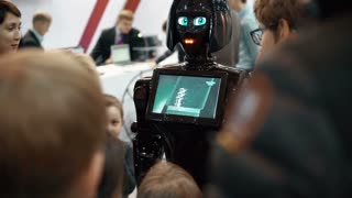 NOVEMBER 5, 2016 RUSSIA, MOSCOW Robotics Expo. Girl robot KIKI in crowd, talking to visitors, show video on screen. 4K