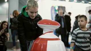 NOVEMBER 5, 2016 RUSSIA, MOSCOW Robotics Expo. Humanoid autonomous robot looking at little boy and speak with him. 4K
