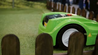 NOVEMBER 5, 2016 RUSSIA, MOSCOW Robotics Expo. Robot lawnmower in grass close-up. Machine cutting grass. 4K