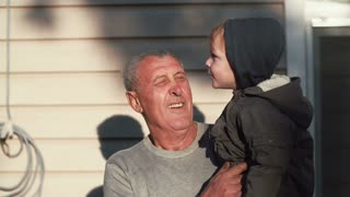 Old man holding little cute boy on hands, looks at him. Grandson points on something with finger, grandfather looks. 4K
