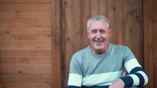 Old man sitting on the porch of the house. Pensioner looking to the camera and laughing, smiling, talking. 4K