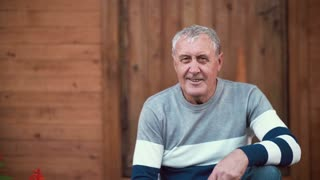 Old man sitting on the porch of the house. Pensioner turns face and looking to the camera, smiling, talking. 4K