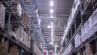 Palettes with cardboard boxes and materials on shelves in a storehouse, slow mo, dolly shoot