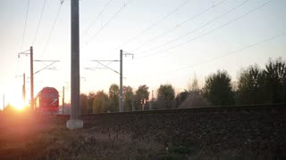 Passenger train passes on the tracks at sunset