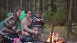 People rest in the nature. Two young women cook marshmallows on open fire in forest. Two kids helping them and eating