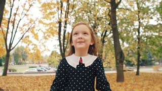 portrait cute little girl with curly hair, in dress with polka dots laugh, jump, have fun in the autumn park slow mo