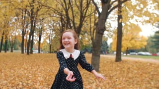 portrait cute little girl with curly hair, in dress with polka dots runing through the autumn alley in the park slow mo
