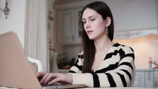 portrait of a beautiful young brunette woman uses laptop in a bright dining.
