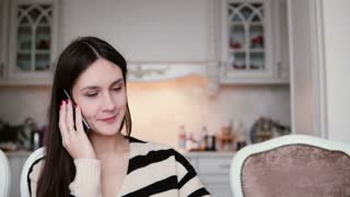 portrait of a beautiful young brunette woman uses smartphone in a bright dining.