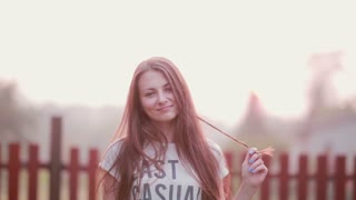 Portrait of beautiful brunette young woman looking at camera, playing with hair, smiling on sunset