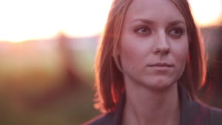 Portrait of young pensive woman at the park in the rays of the setting sun, looking into the distance, close-up, slow mo