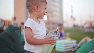 Pretty little boy having fun at the park in summer day, holding a glass with straws and laughing.