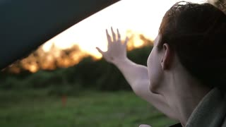 Pretty woman in a car enjoying the wind, hand playing in the air. Sun sets in the countryside. Wind blows hair. Slow mo