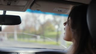 Pretty woman is sitting in a car. She looks in the window, turns her head and talks to the driver, Traveling by car.