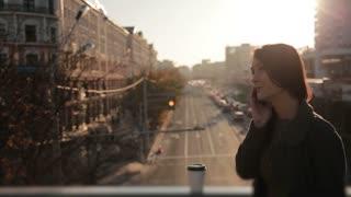 pretty woman talking on the phone on a city bridge