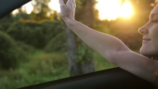 Pretty woman traveling by car in summer. Hand playing with wind through the window of a car. Beautiful nature. Slow mo