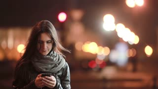 Pretty young woman makes a phone call. She cheerfully talks on the phone in the street at cold night. Then goes away.