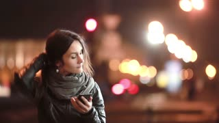 Pretty young woman makes a phone call. She talks on the phone in the street at cold night. Modern technology.