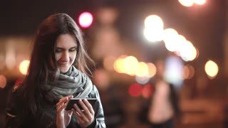 Pretty young woman using her smartphone at night. Lady in the street in cold weather. Modern technology.