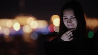 Pretty young woman using tablet, smiling at night. Blurred coloured city lights at the background. Modern technology.
