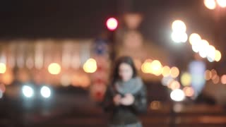 Pretty young woman walking in the street, slowly getting in focus. Smiling lady using her smartphone. Modern technology