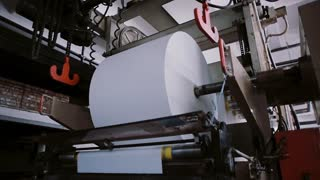 Printing machine work. A big roll of paper for publishing. Printing establishment detail on production line with sound.