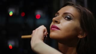 Putting make-up on young beautiful womans face while preparing for a contest. Backstage of competitions