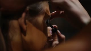 Putting mascara on womans eyelashes. Make-up artist at work. Preparing for a contest. Sideview of a womans face.
