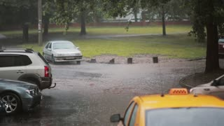 Rain pouring down on pavement, a taxi and cars turns into flood. Another car passes by, water under it splashes around.