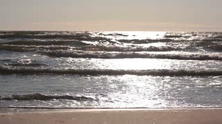 Sea waves are lit by the sun and are running close to the camera