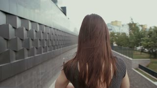 sexy business woman standing on a bridge overlooking the road, steadicam shot. slow mo