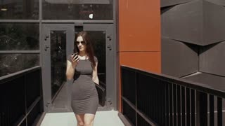 sexy business woman using smartphone walking near under construction business building, steadicam shot. slow mo