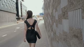sexy business woman walking on a sidewalk in business center of the city with her briefcase, steadicam shot. slow mo