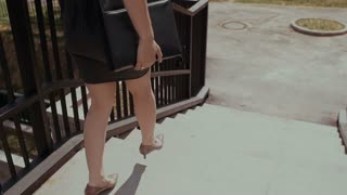 sexy business woman walking on a sidewalk in city urban street with her briefcase, steadicam shot. slow mo