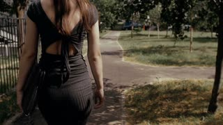sexy business woman walking on a sidewalk in urban street with her briefcase, steadicam shot. slow mo