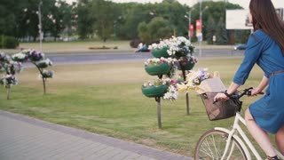 Side and back view of a girl riding a bike near driven cars with flowers in a basket, slow mo, steadicam shot