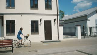 Side view of a brunette girl riding a bike near old buildings as people walk by, slow mo, steadicam shot
