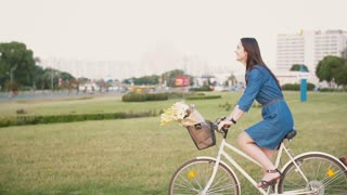 Side view of a brunette girl with long hair riding a bike in the city with flowers in a basket, slow mo, steadicam shot