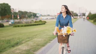 Side view of a girl cycling with flowers in a basket and exploring the city, slow mo, steadicam shot