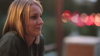 Side view of beautiful young woman sitting in cafe and looking into the distance. Close-up, blurred lights, urban street
