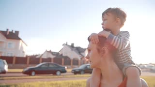 Side view of family spending time together on a sunny summer day. Cute little boy sits on his moms shoulders. Slow mo