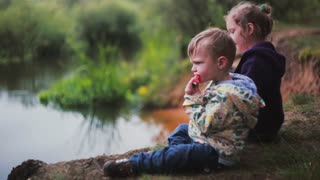 Side view of two cute little kids, a boy and a girl, eating watermelon, sitting on a river bank.